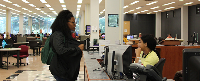 Help Desk worker helping student in Middleton Library